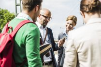 Businesspeople with cell phone talking outdoors — Stock Photo