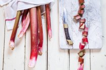 Ruibarbo picado con tallos y tabla de cortar de madera con cuchillo en madera blanca - foto de stock