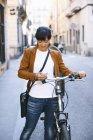 Mulher sorridente com bicicleta e celular na cidade — Fotografia de Stock