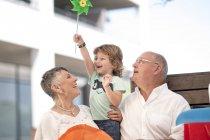 Großvater und Großmutter Holding Enkel mit Papier Windmühle — Stockfoto