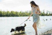 Молода жінка, прогулянки з собакою на Ріверсайд — стокове фото