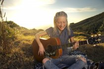 Happy young woman playing guitar on blanket in meadow — Stock Photo