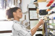 Junge Näherin mit Klöppeln Wahl Farbe in Werkstatt — Stockfoto