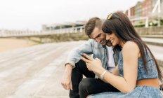Jovem casal apaixonado olhando para smartphone — Fotografia de Stock