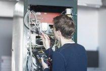 Techniker, die Installation mit Messgerät prüfen — Stockfoto