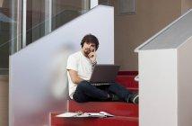 Замислений молода людина з навушниками і ноутбук — стокове фото