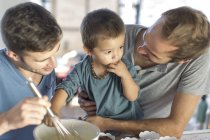 Gay couple baking cake with son — Stock Photo