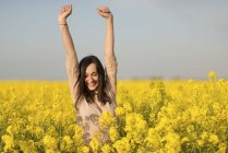 Happy woman in a blossoming rape field — Stock Photo