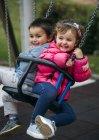 Niña y niño sentado y riendo en el columpio - foto de stock