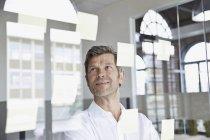 Empresário com notas autoadesivas na vidraça no escritório — Fotografia de Stock