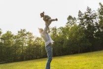 Pai, levantando a filha no Prado — Fotografia de Stock