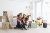 Young couple in new flat with cardboard boxes, sitting on floor — Stock Photo