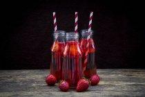 Tre bottiglie di vetro di limonata di fragole e fragole fresche sulla tavola di legno — Foto stock