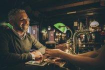 Усміхнений чоловік сидить на лічильник паб — стокове фото