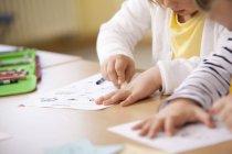 Закри школярки працює над роботою листів в класі — стокове фото