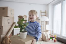 Little blond boy helping with cardboard boxes — Stock Photo