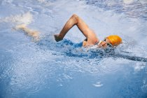 Mature caucasian male triathlet swimming in a pool — Stock Photo