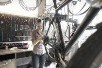 Giovane donna che lavora in un negozio di riparazione di biciclette — Foto stock