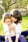 Дві сестри, сидять разом на галявині в саду — стокове фото