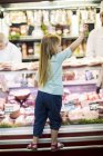 Little girl standing on counter of butchery — Stock Photo