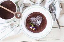 Шоколадный пудинг, съедобные цветы в пластине — стоковое фото