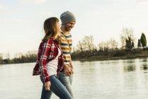Joyeux jeune couple au bord de la rivière marchant main dans la main — Photo de stock