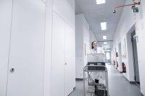 Jovem cientista feminina trabalhando no laboratório biológico, empurrando o carrinho — Fotografia de Stock