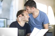 Happy gay couple with document kissing — Stock Photo