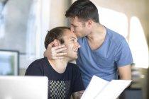 Casal gay feliz com documento beijando — Fotografia de Stock