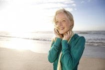 Smiling young woman on beach at sunrise using cell phone — Stock Photo