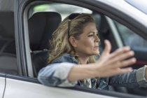 Frustrated woman in car stuck in traffic jam — Stock Photo