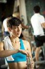 Frau öffnet Wasserflasche in Turnhalle mit Sportlern im Hintergrund — Stockfoto
