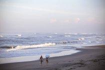 Индонезия, Бали, две женщины, перевозящих доски для серфинга на пляже — стоковое фото
