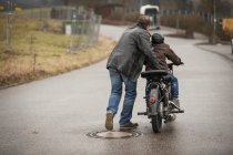 Father and son driving with vintage moped — Stock Photo