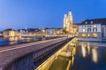 Svizzera, Zurigo, Muenster ponte sul fiume Limmat, Limmatquai e grande Minster sullo sfondo illuminato di sera — Foto stock