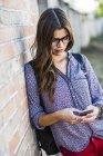 Брюнетка в очках, смотрит на мобильный телефон — стоковое фото