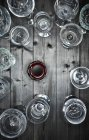 Glass of red wine and empty wine glasses on wood — Stock Photo