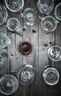 Стакан красного вина и пустые бокалы вина на дереве — стоковое фото
