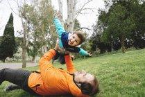 Батько, граючи з маленький син у парку — стокове фото