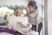Senior woman and adult daughter working on sewing machine — Stock Photo