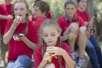 Enfants et femme mangeant des fruits à l'extérieur — Photo de stock