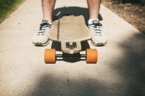 Close up of male feet with longboard — Stock Photo