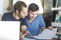Due uomini con laptop e documenti — Foto stock