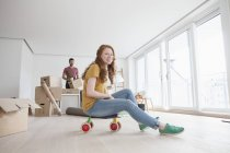 Young couple moving into new flat, woman sitting on toy cart — Stock Photo