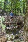 Греція, Родос, молодий чоловік, що стоїть на дерев'яний міст у лісі — стокове фото