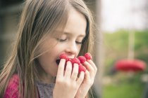 Ragazza mangiare lamponi dalle dita all'aperto — Foto stock
