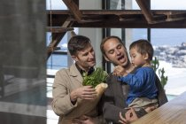 Gay couple and kid at home with groceries — Stock Photo