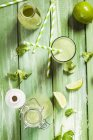 Green smoothie with lambs lettuce, parsley, limes and banana on green wood — Stock Photo