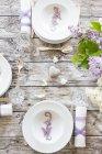 Puso la mesa de madera decorada con flores lilas - foto de stock