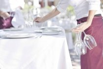 Waiter placing wine glasses on outdoor restaurant table — Stock Photo
